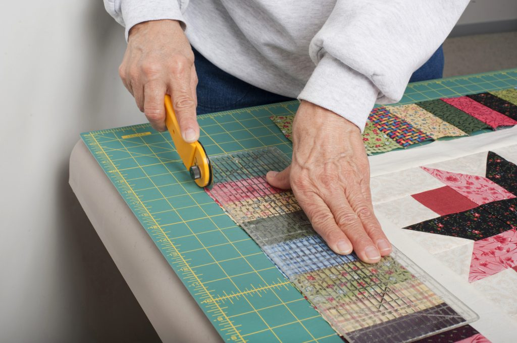 quilter cutting a quilt with a rotary cutter and cutting mat